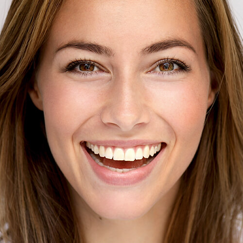 Close-up of a woman smiling with perfect teeth. She is happy due to the sedation options available at our office