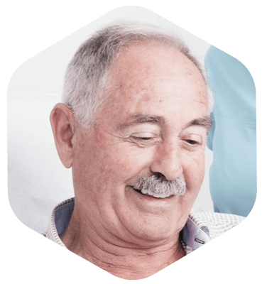 Older male patient looking down and smiling after he received a dental implant from Dr. Khayat
