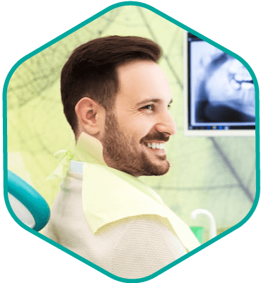 Male patient in the dentist chair with his digital x-rays showing on the treatment room monitor