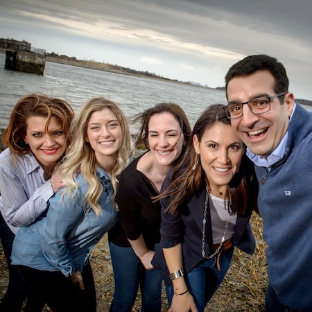 A group shot of your Hingham MA dentists, Dr. Khayat, and Dr. Becerra with their dental team on the beach.