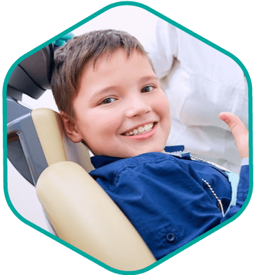 Young patient sitting in the dentist chair and showing his thumbs up because he now has sealants