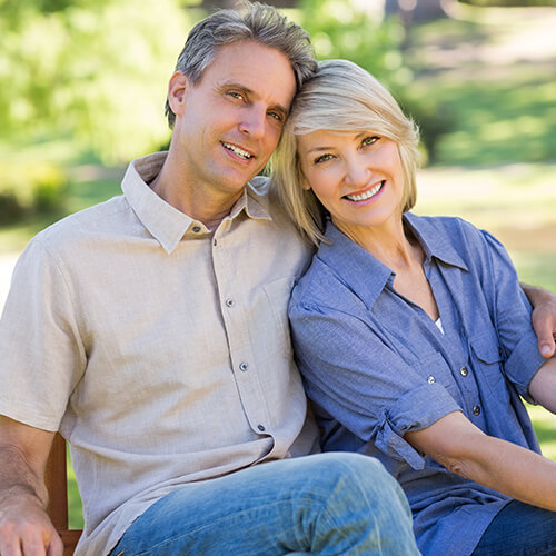 Middle-aged couple sitting on a bench smiling because of the options available at South Shore Prosthodontics