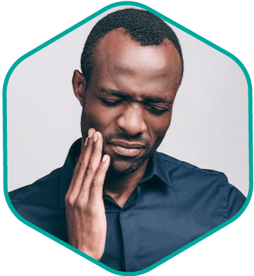 Male professional holding his jaw due to TMJ pain