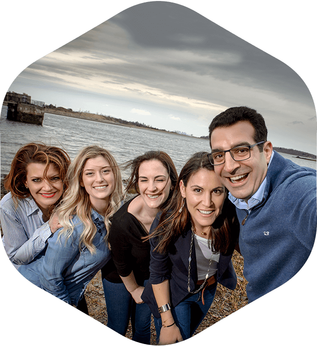 The dental team of SouthShore Prosthodontics smiling and leaning in for a selfie photo down by the water