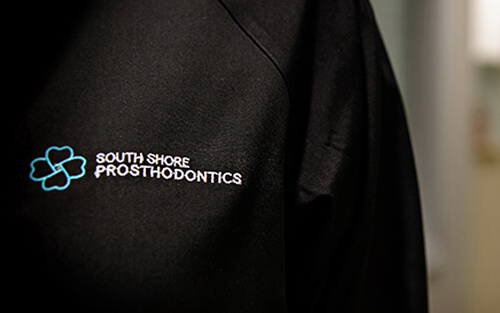 Close up of our team uniforms showing our South Shore Prosthodontics logo
