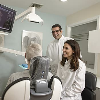 Dr. Khayat and Dr. Becerra, smiling and talking to a patient while standing at our front desk